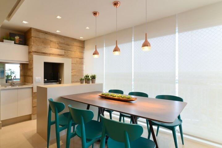 Varanda com churrasqueira com cadeiras azul turquesa Projeto de Danyela Correa
