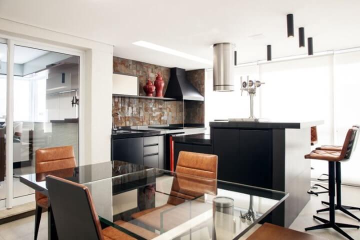 Varanda com churrasqueira com cadeiras de couro Projeto de Carolina Vilela