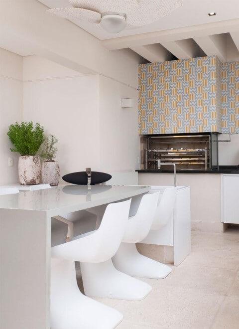 Varanda com churrasqueira com decoração clara Projeto de Olegário de Sá