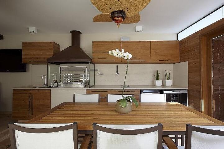 Varanda com churrasqueira com decoração em madeira Projeto de Patricia Covolo