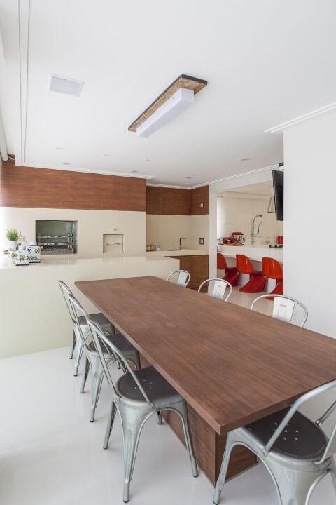 Varanda com churrasqueira com mesa de madeira e cadeira industrial Projeto de Mariana Luccisano