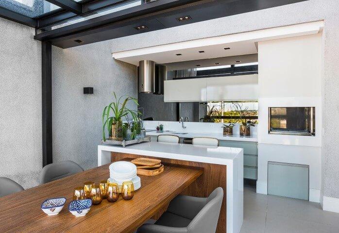 Varanda com churrasqueira com mesa de madeira e poltronas Projeto de Leonardo Muller
