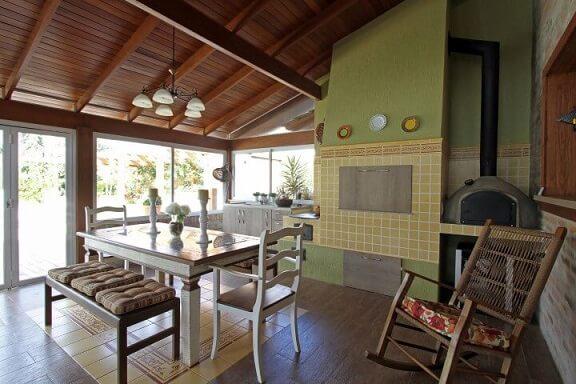 Varanda com churrasqueira com mesa e bancos em madeira branca Projeto de Graça Brenner