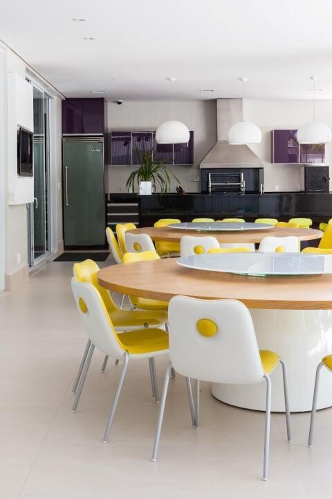 Varanda com churrasqueira com mesa redonda com cadeira amarela Projeto de Olegário de Sá