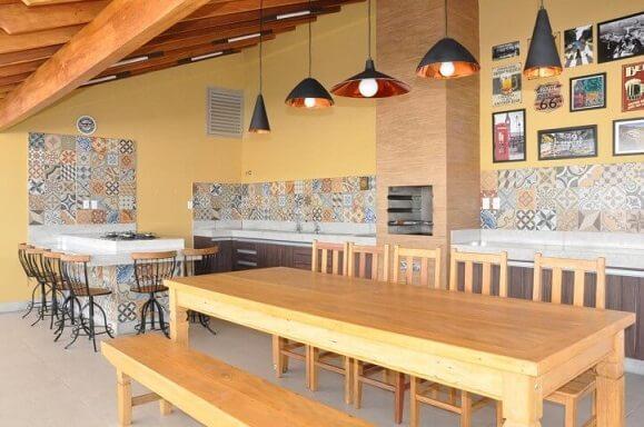 Varanda com churrasqueira com mesas grandes Projeto de Claudia Breias
