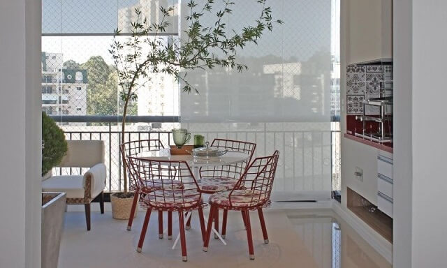 Varanda com churrasqueira com mesinha vermelha Projeto de Marcia Ácaro