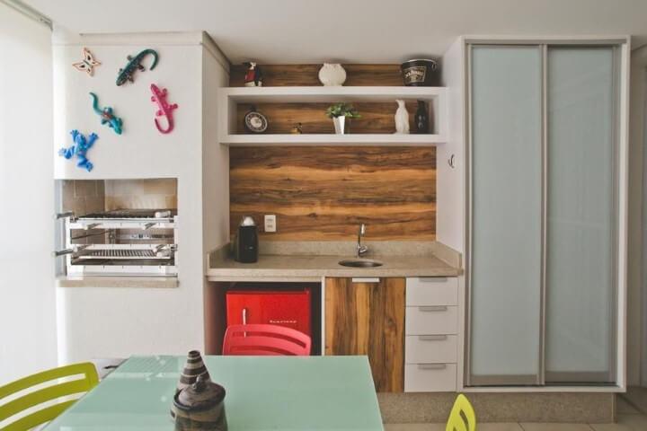 Varanda com churrasqueira com objetos decorativos acima Projeto de Cristina Muss