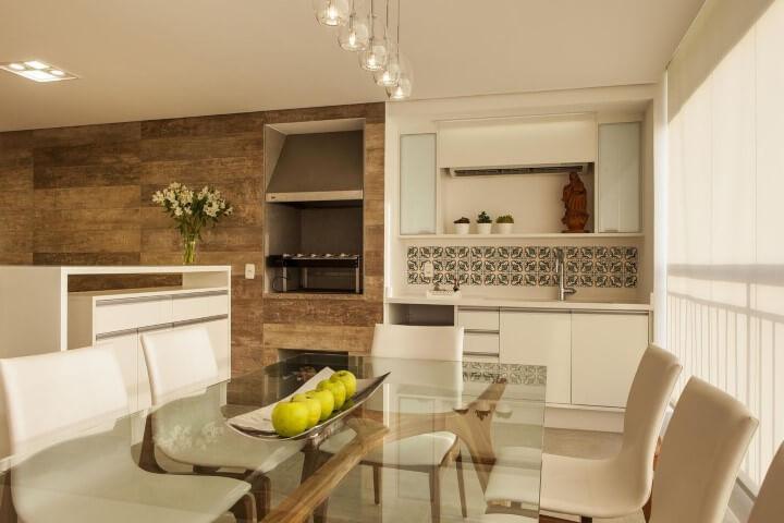 Varanda com churrasqueira com parede revestida de madeira Projeto de Lilian Barbieri