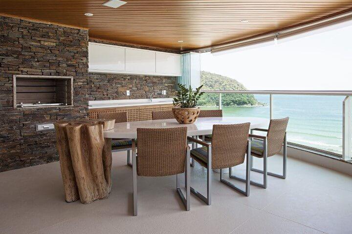 Varanda com churrasqueira com revestimento de pedra Projeto de Korman Arquitetos