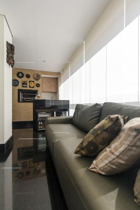 Varanda com churrasqueira com sofá Projeto de Fernanda Duarte
