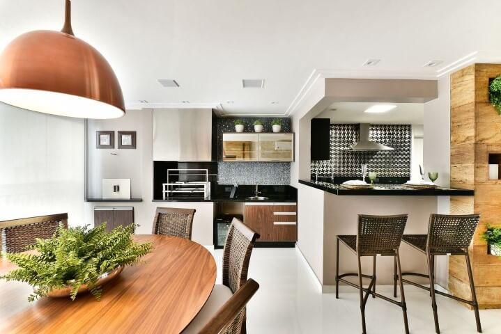 Varanda com churrasqueira integrada à cozinha Projeto de Tetriz Arquitetura
