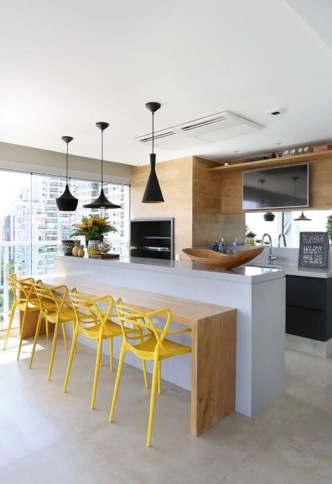 Varanda com churrasqueira pequena com cadeiras amarelas Projeto de Karen Pisaca