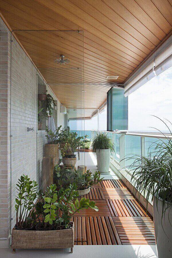 Varanda com cortina de vidro e deck de madeira