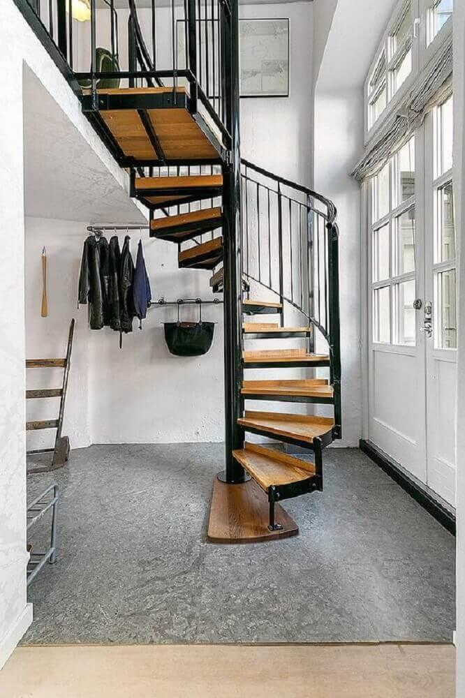 casa minimalista com escada caracol de ferro com degraus de madeira