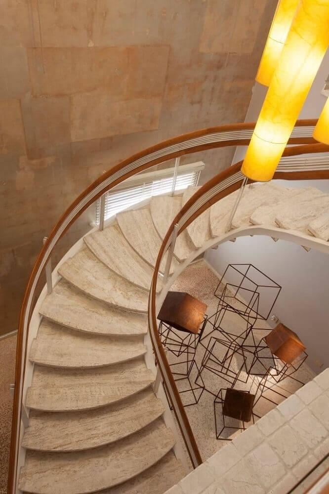 Modelo de escada caracol de concreto com corrimão de madeira.