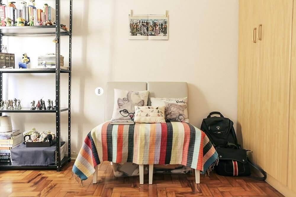 Decoração simples com sofá pequeno e armário de ferro.