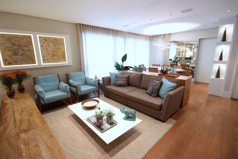 decoração de sala de estar com sofá marrom e almofada azul