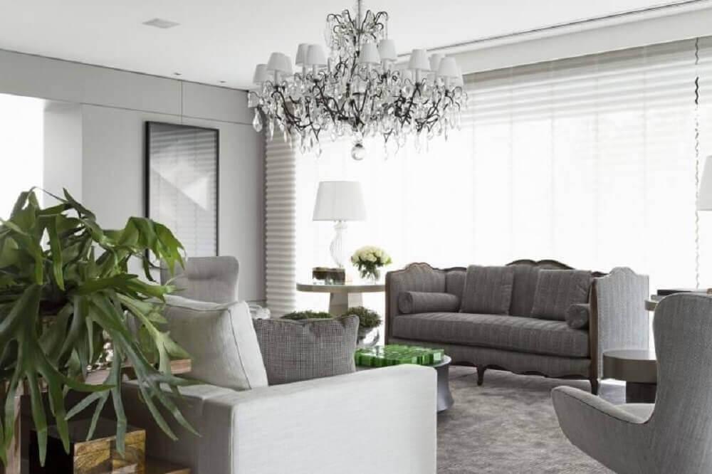 Decoração de sala com lustre sofisticado e sofá cinza
