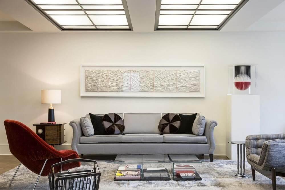 Decoração de sala de estar com sofá cinza e almofada redonda.