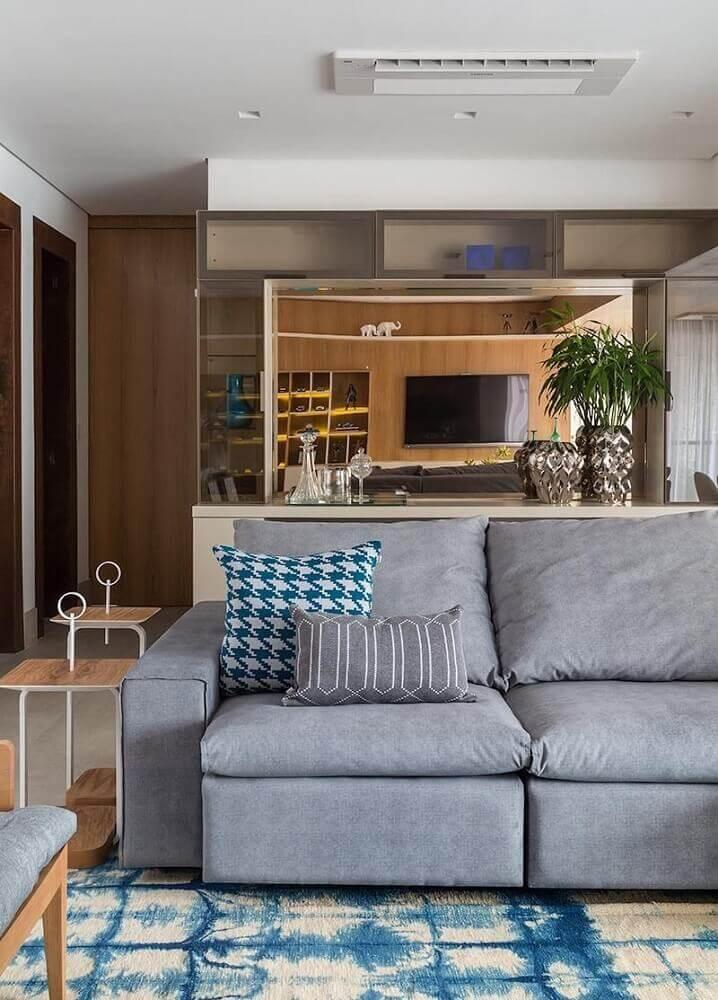 sala de estar com sofá retrátil cinza e almofadas estampadas