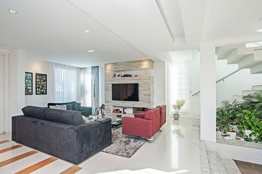 Decoração de sala com sofá cinza e poltrona vermelha