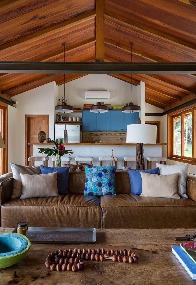 sala com sofá marrom com almofadas em tons de cinza e azul