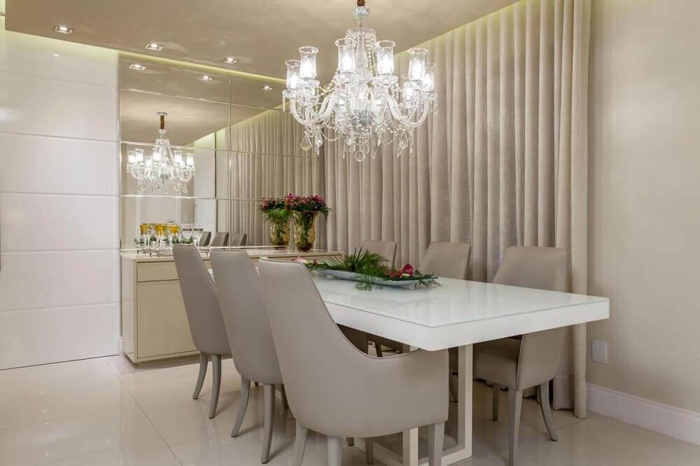 Decoração clean com espelho para sala de jantar e lustre