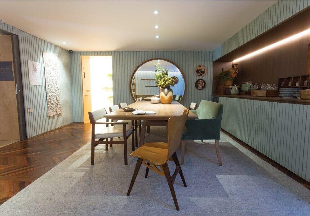 Decoração de sala de jantar com espelho grande e redondo.
