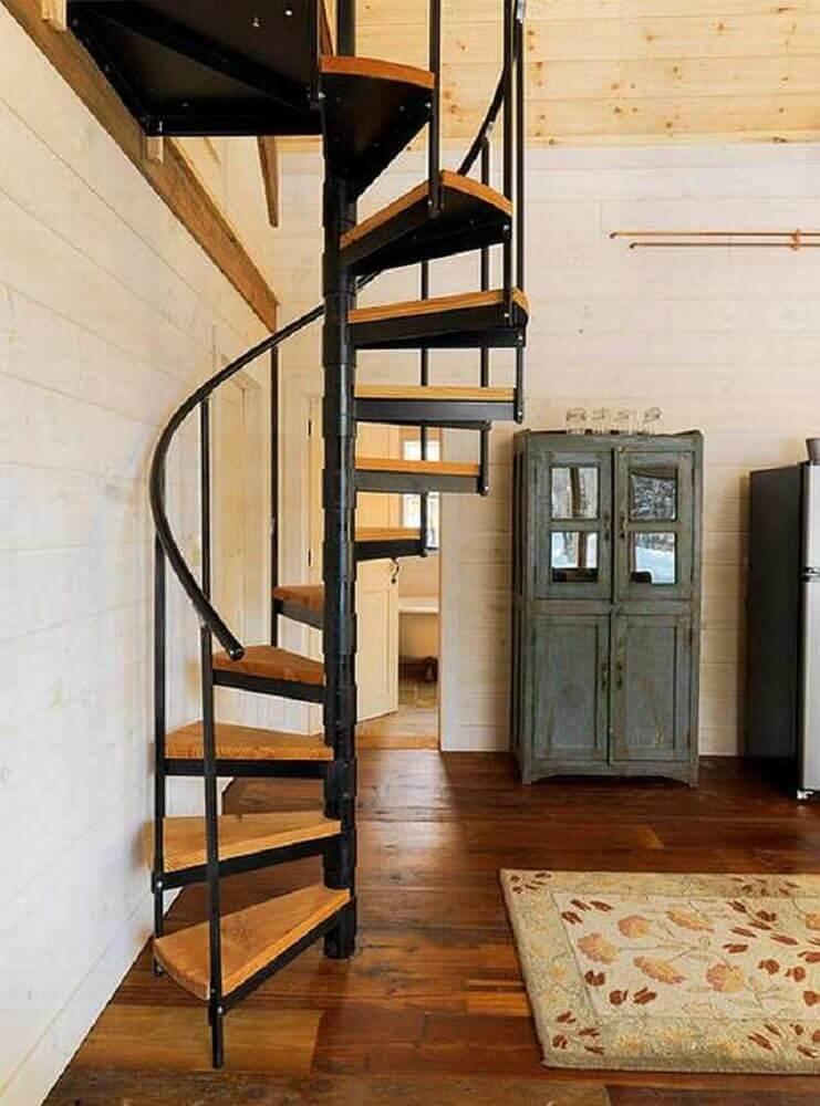 Casa com escada caracol de ferro com degraus de madeira.