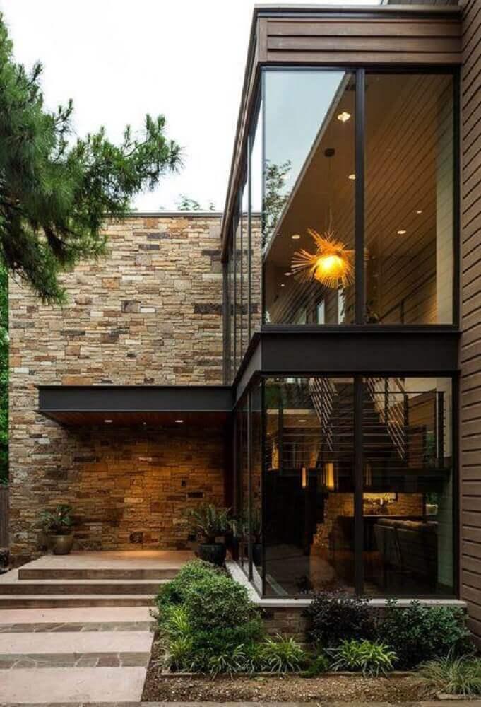 fachada de casa com paredes de vidro e pedra