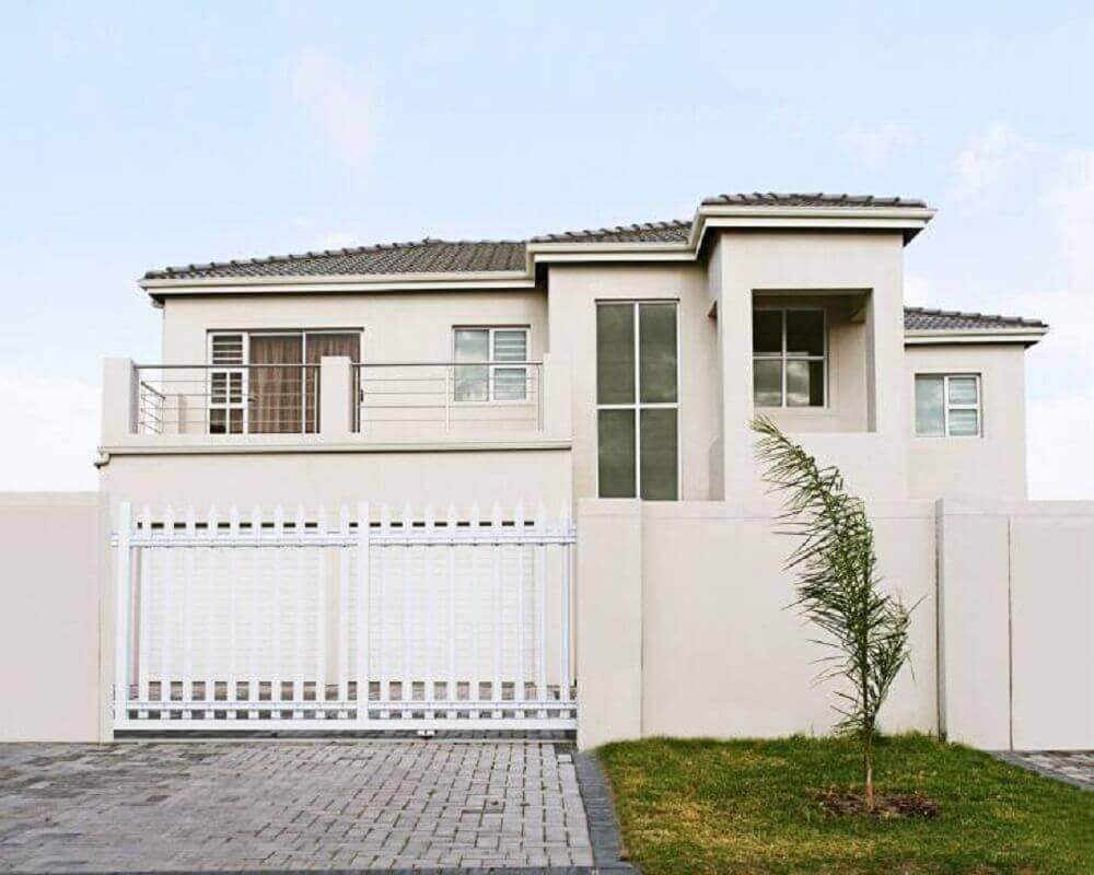 Frente de casas com muro e portão branco.