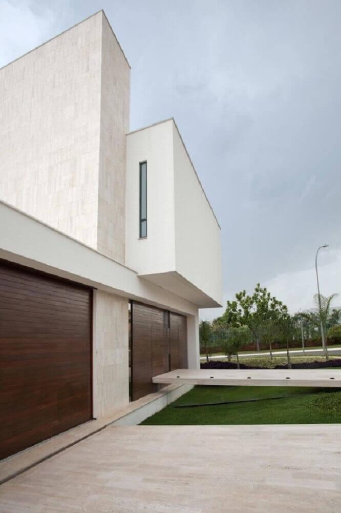 fachada de muro minimalista com portão de madeira