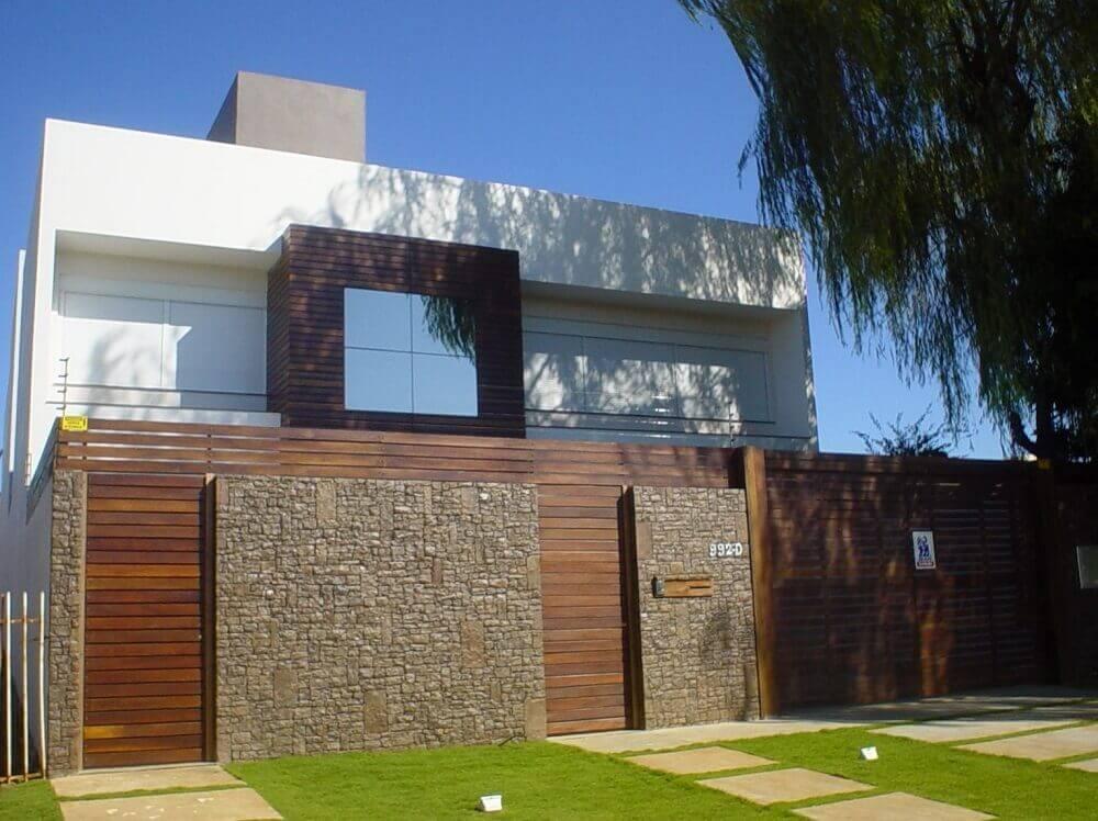 frente de casas com muro de pedra e madeira