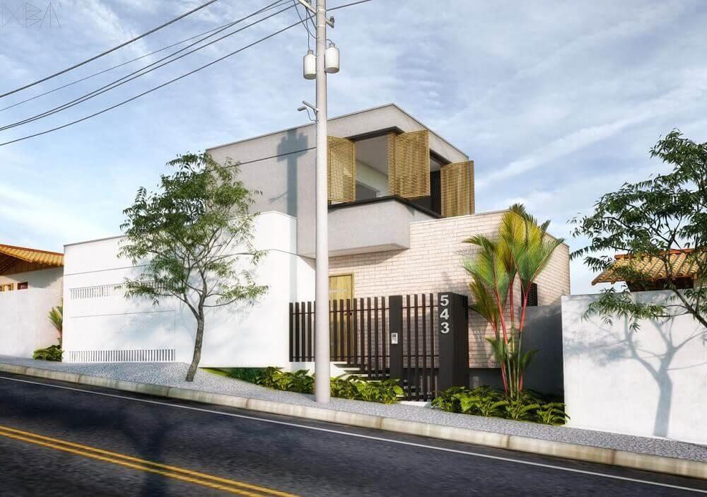 Frente de casas com muro e parede de tijolo à vista