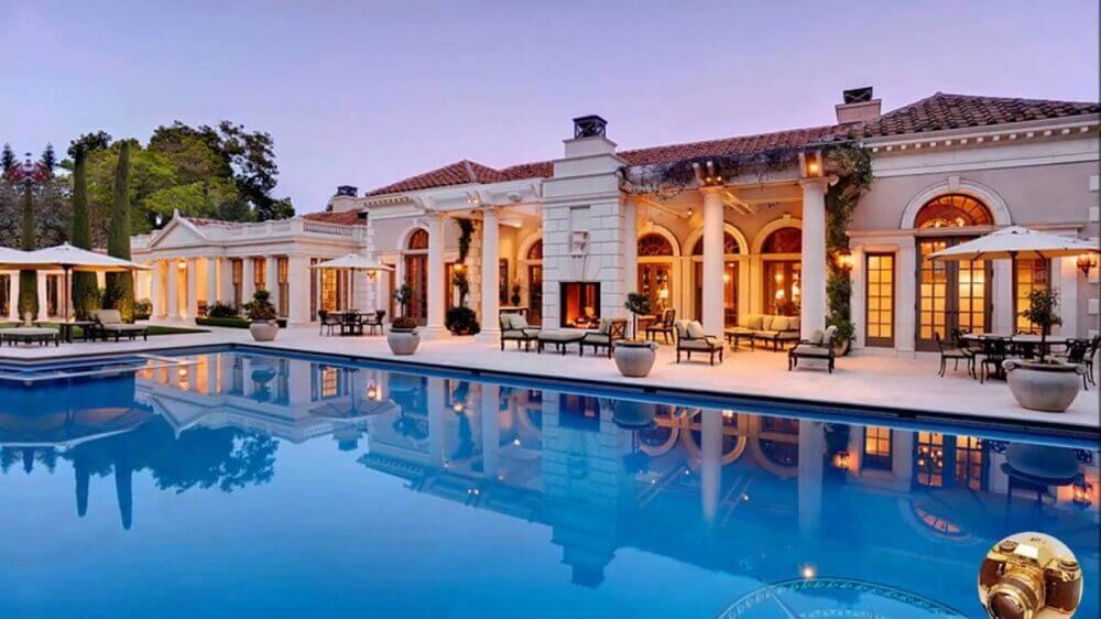 mansão com fachada branca e grande piscina