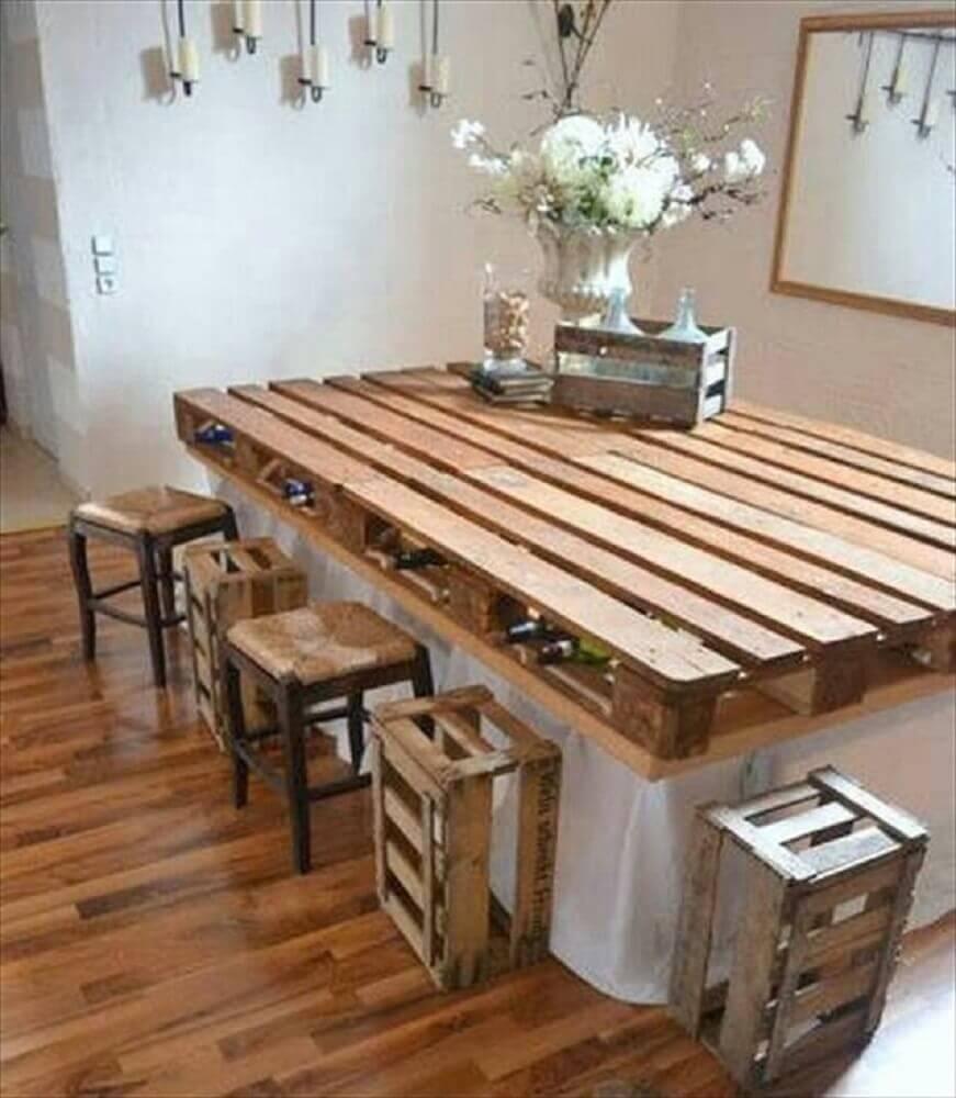 Mesa feita de pallet com espaço para guardar vinhos