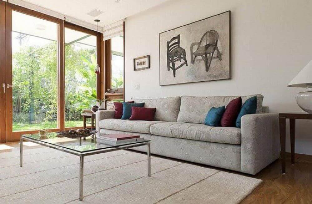 Sala de estar decorada com modelos de mesa de vidro com estrutura de metal