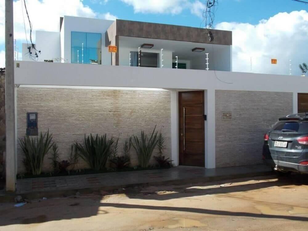 Muros de casa com pedra cajiquinha e pequeno jardim