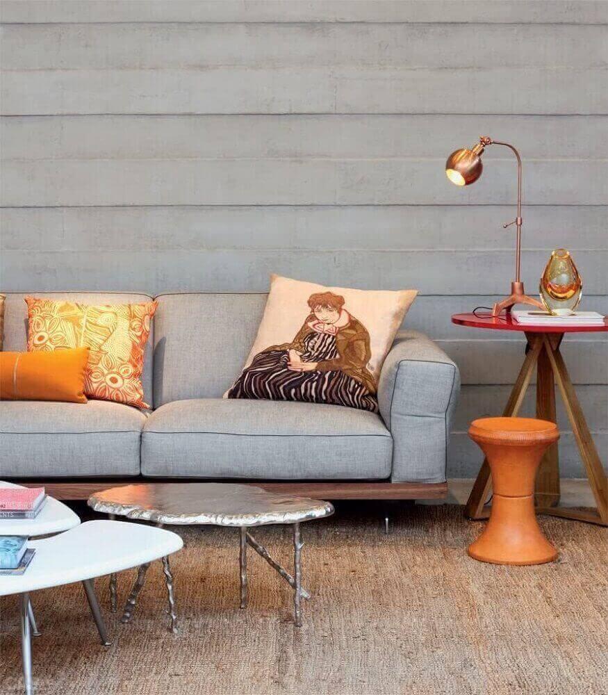 Sala com luminária e almofadas para sofá cinza.