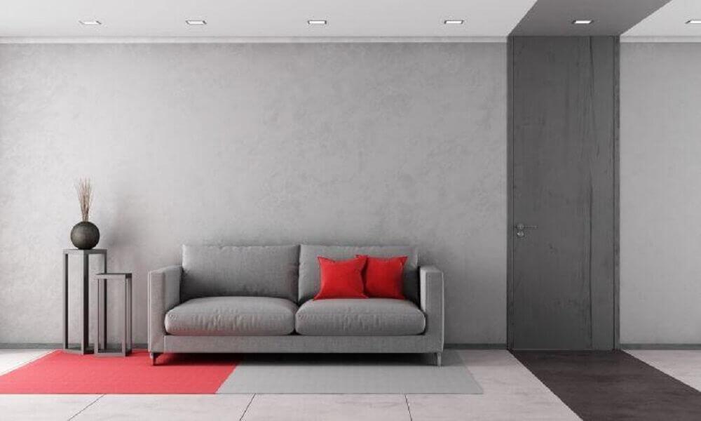 sala com parede cinza com tonalidades diferentes e almofadas vermelhas