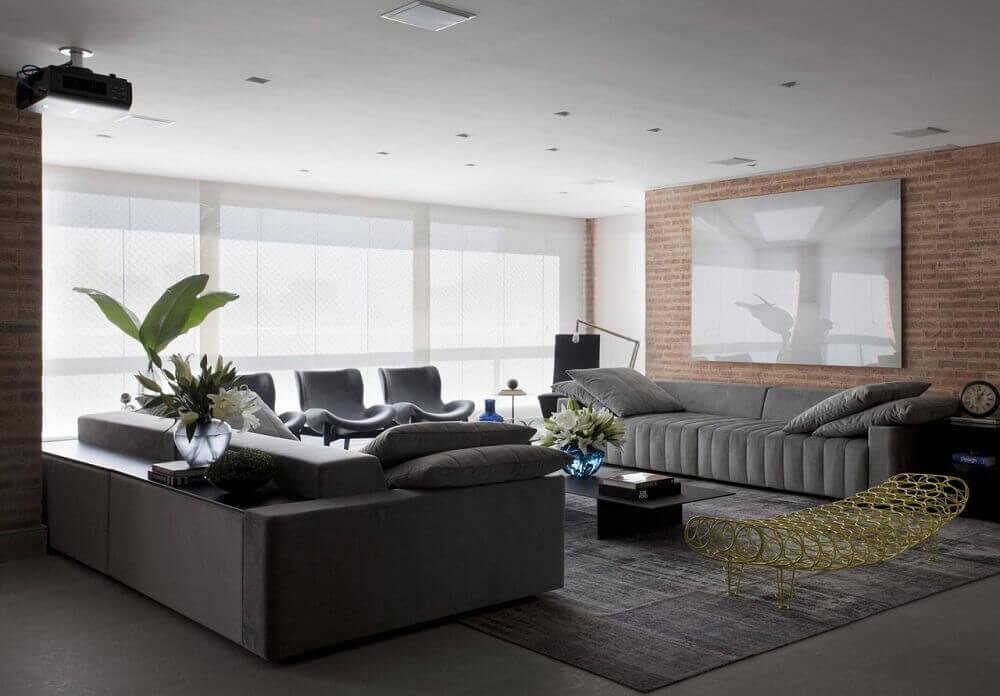 sala com sofá cinza e parede de tijolinho