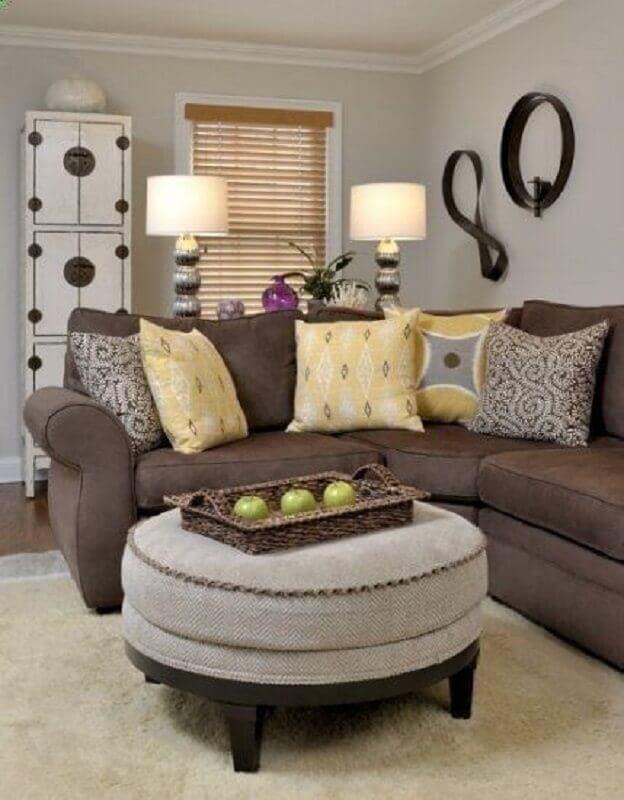 sala com sofá marrom e almofadas amarelas estampadas