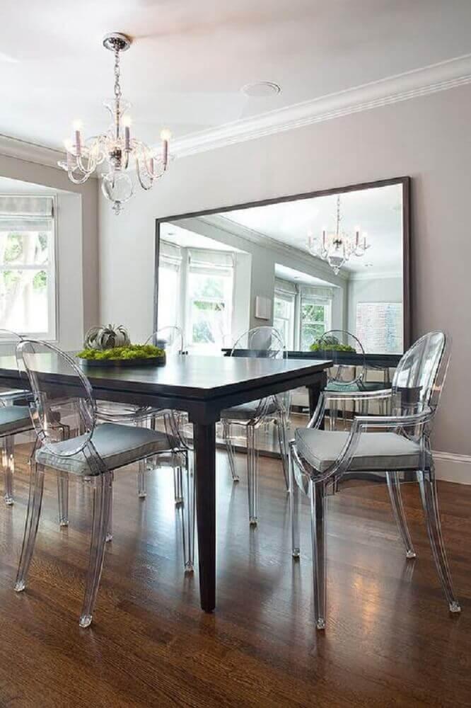 sala de jantar com espelho apoiado no piso e cadeiras de acrílico