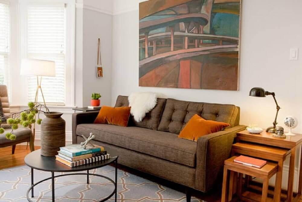 sofá marrom com almofadas laranja e manta peluda