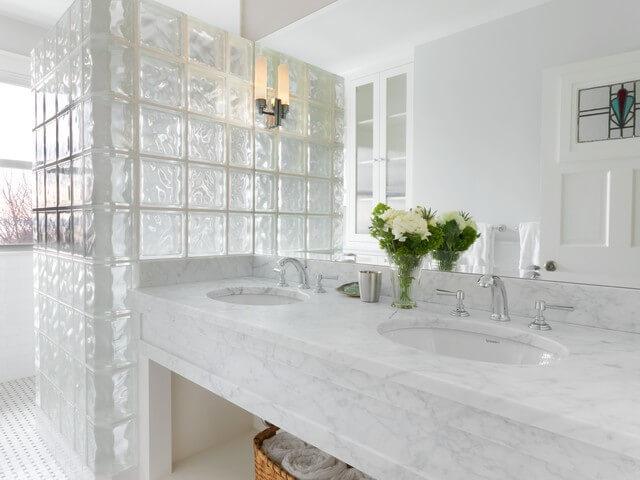 Banheiro com divisória de tijolo de vidro