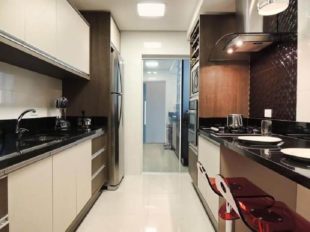 Cozinha planejada com banquetas de acrílico vermelho