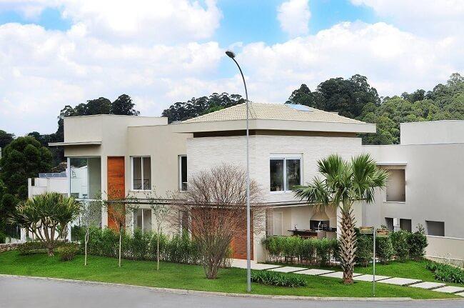 Frente de casas com pintura neutra e telhado colonial claro