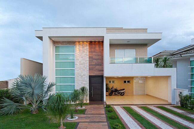 Frente de casas com garagem aberta e jardim