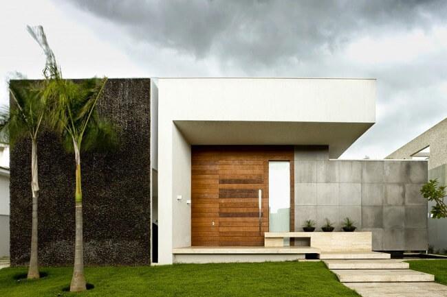 Parede com revestimento cinza e porta de madeira decora frente de casas
