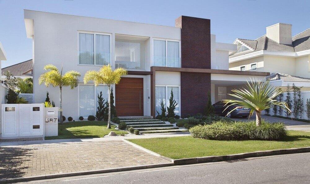 Fachada de casas com platibanda e jardim na entrada